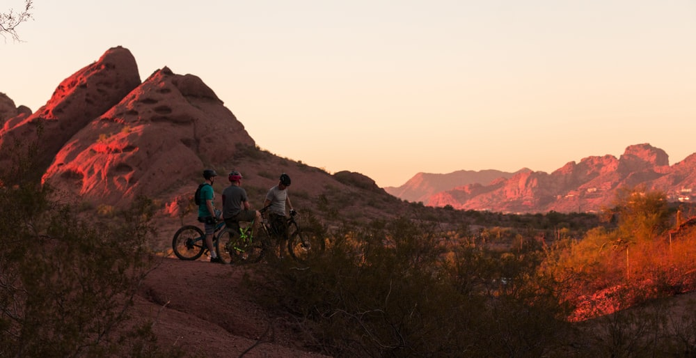 three men with their bicycle looking at rock formations \