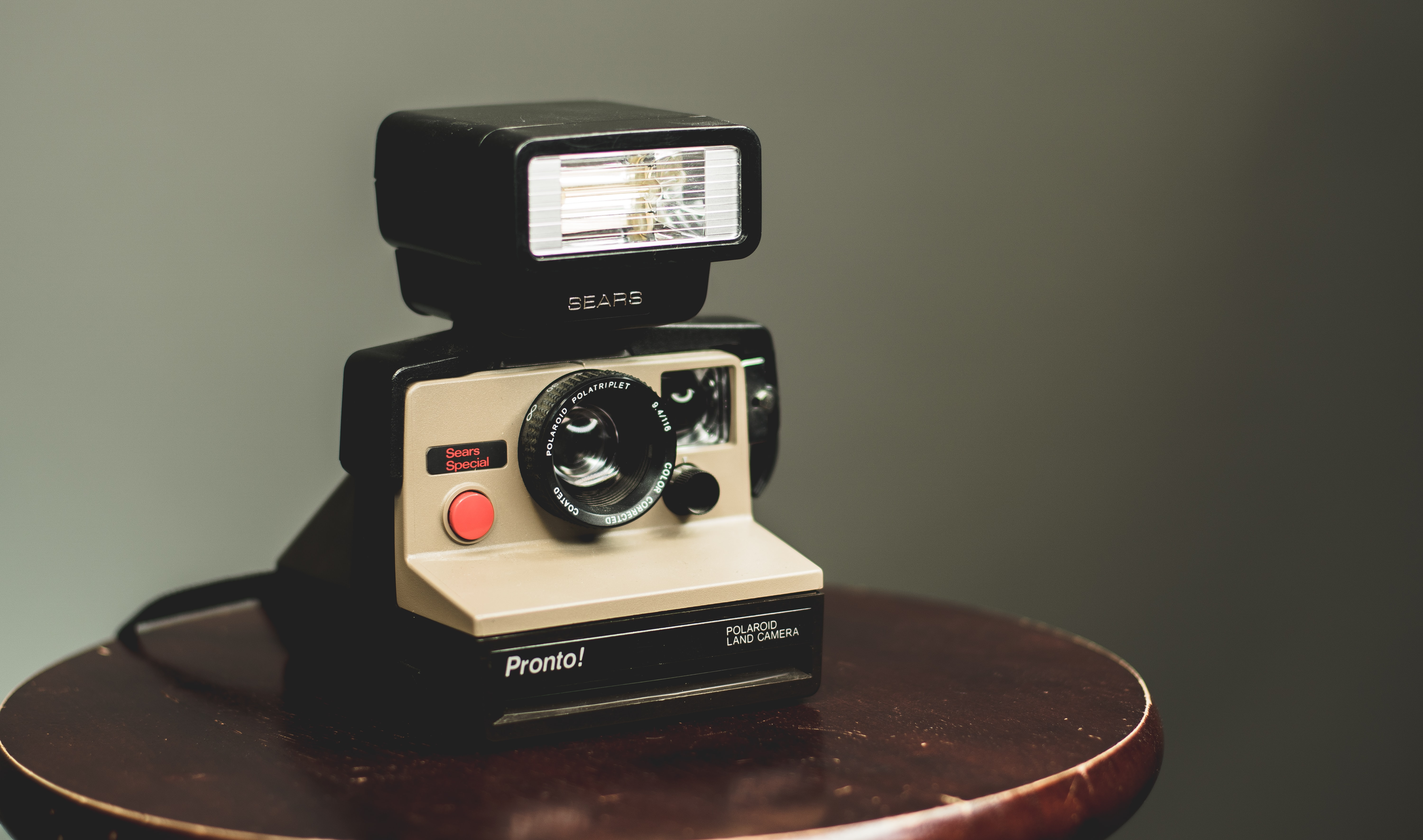 white and black camera on top of brown wooden table