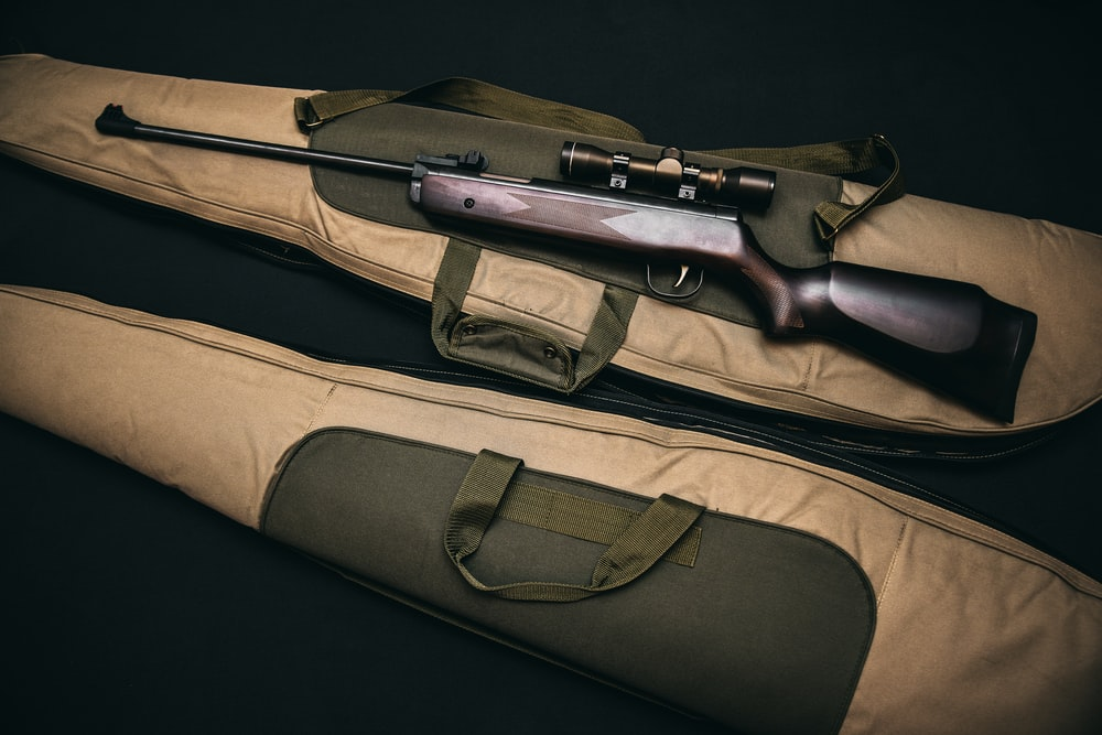Brown And Black Sniper Rifle With Beige Bag