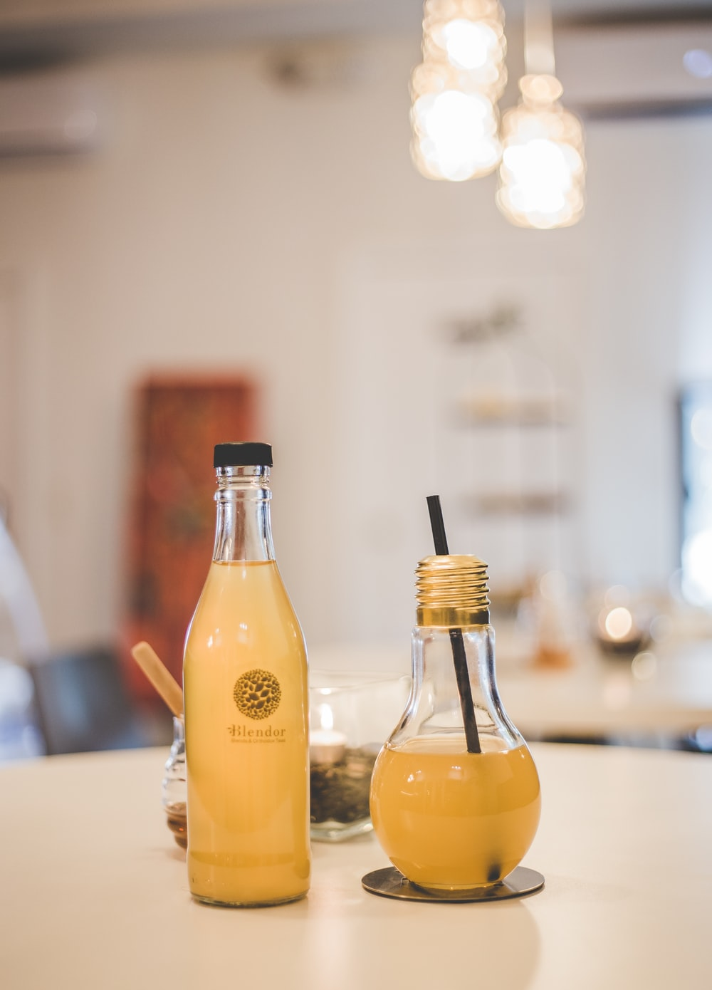two clear glass bottles with beverage on table