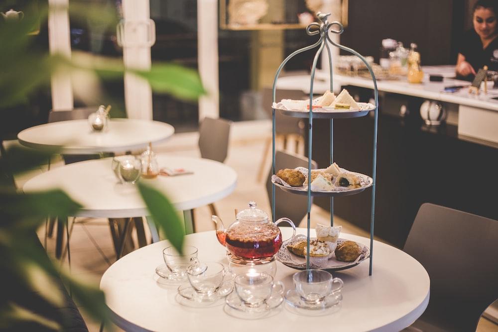 tea set beside gray 3-tier rack on round white table