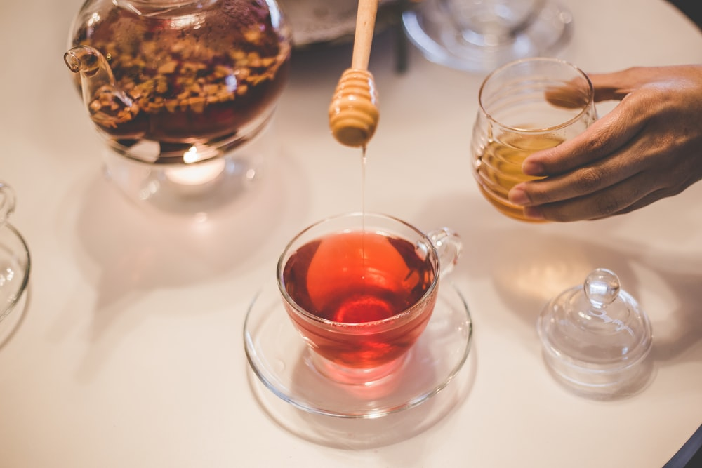 person putting honey on tea