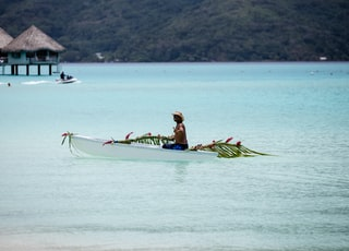 person riding on boat near hut