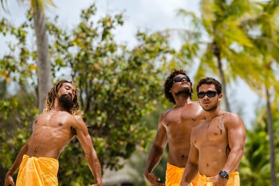 three topless men bora bora teams background