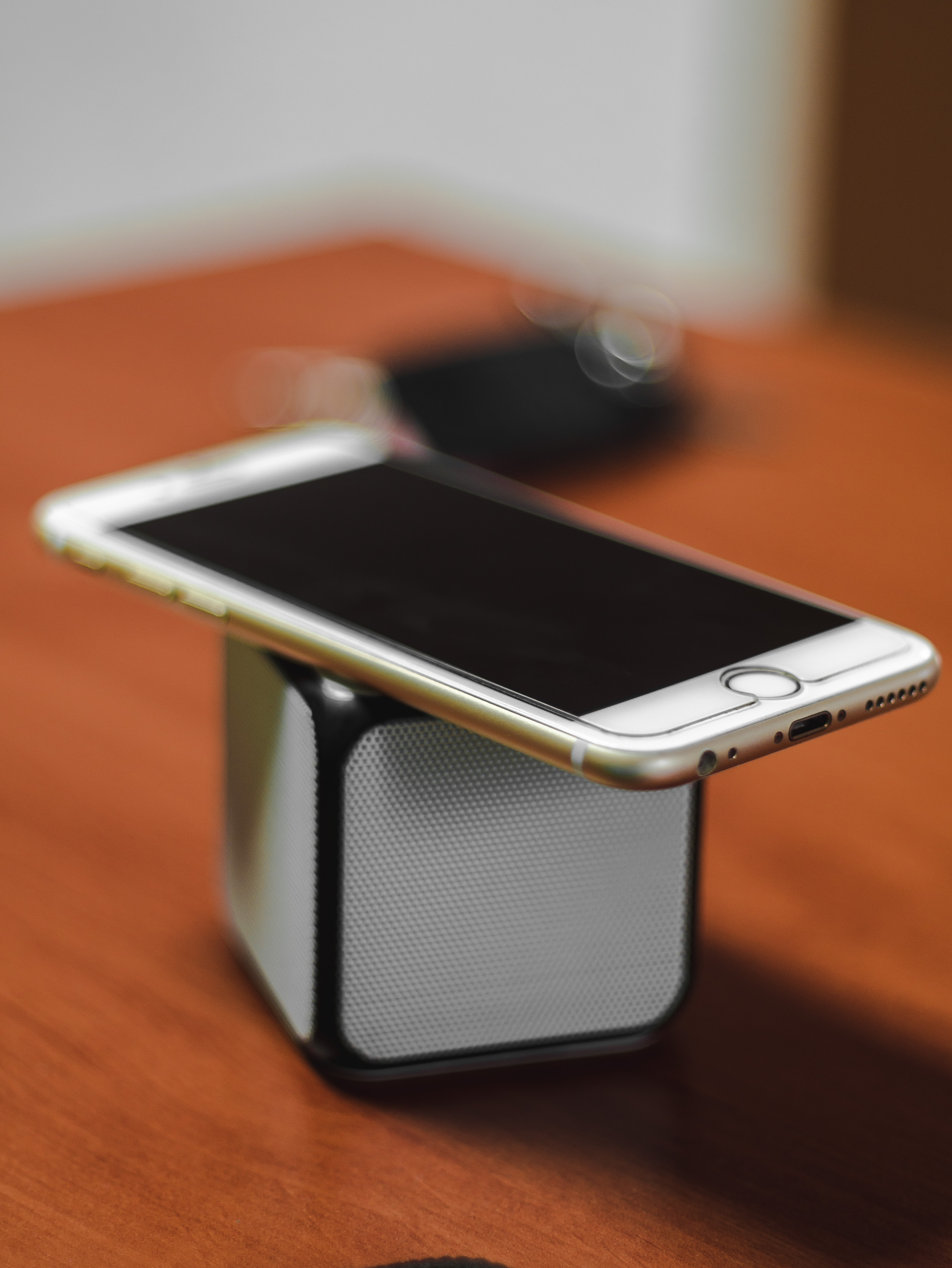 gold iPhone 6 on top of Bluetooth portable speaker