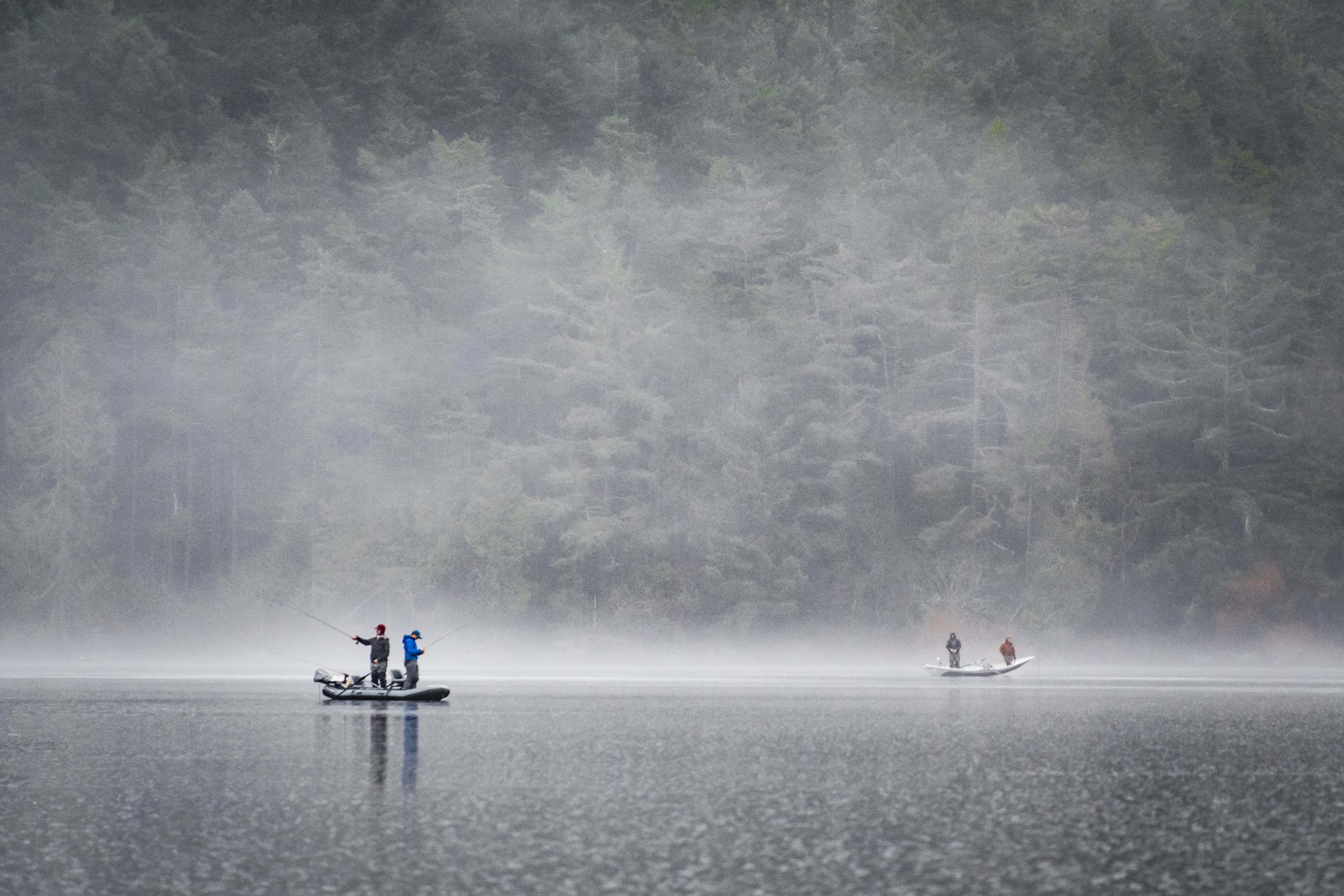 people on boat fishing near foggy forest
