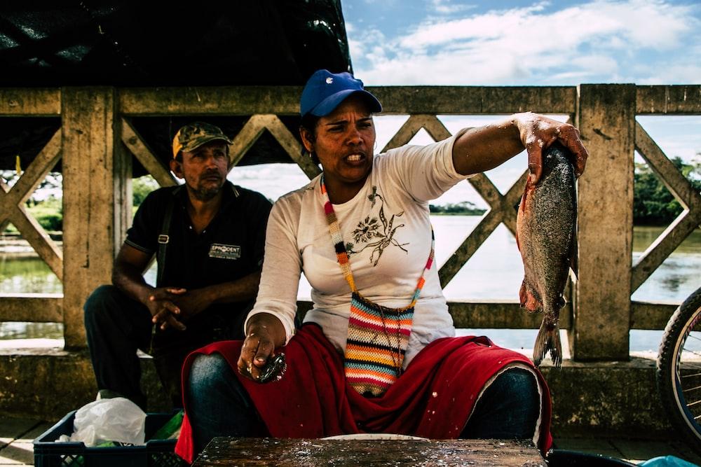 woman holding gray fish