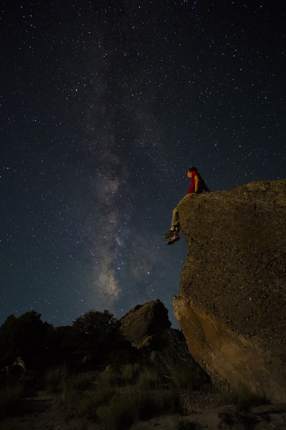 person sitting on edge of large rock under starry night sky