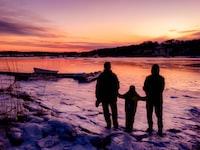 three person standing near boat