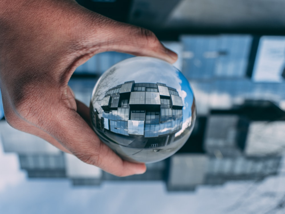 person holding a clear glass ball