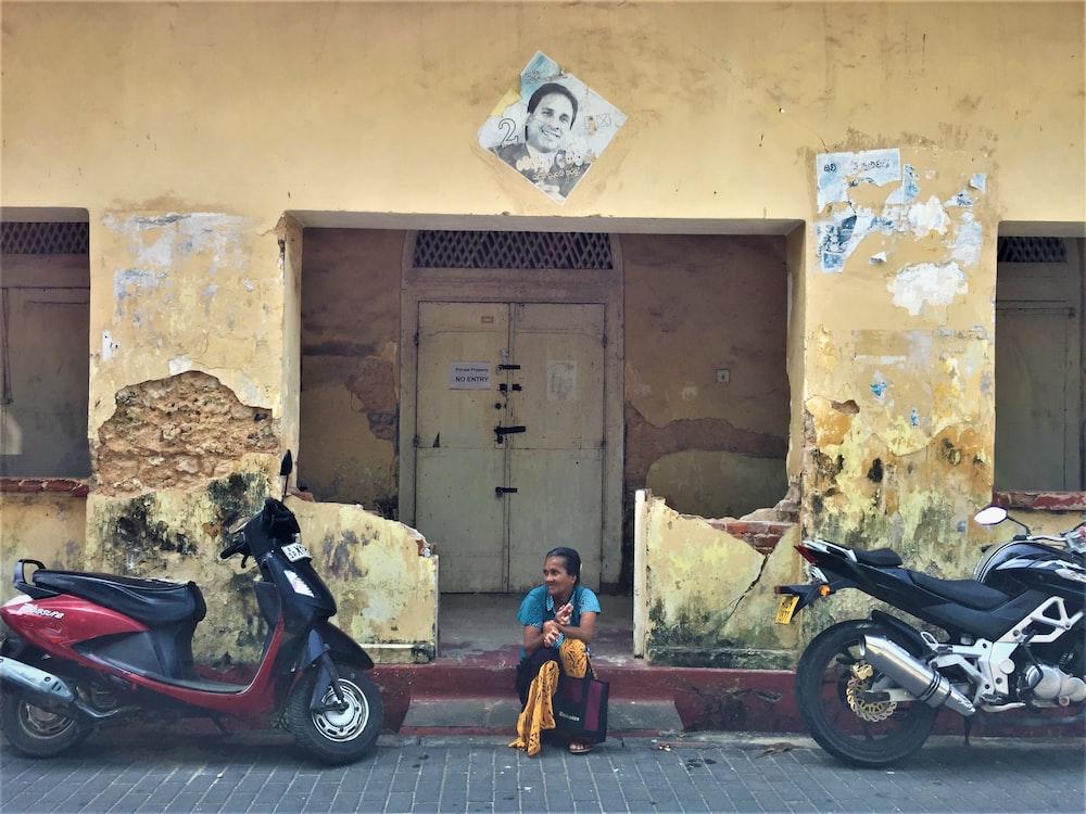 woman sitting between motorcycles