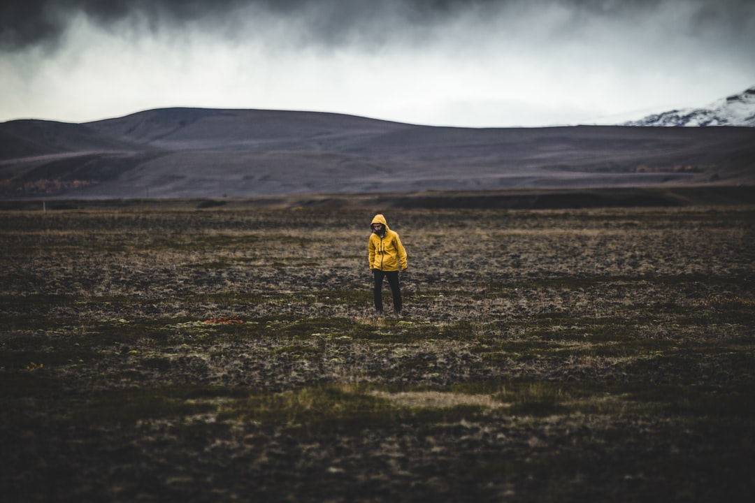 Iceland Wanderer with Yellow Jacket. Exploring fields in wasteland.