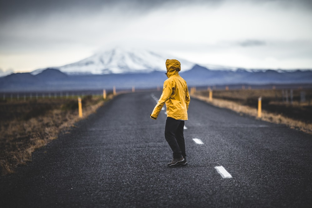 man standing on the middle of the road