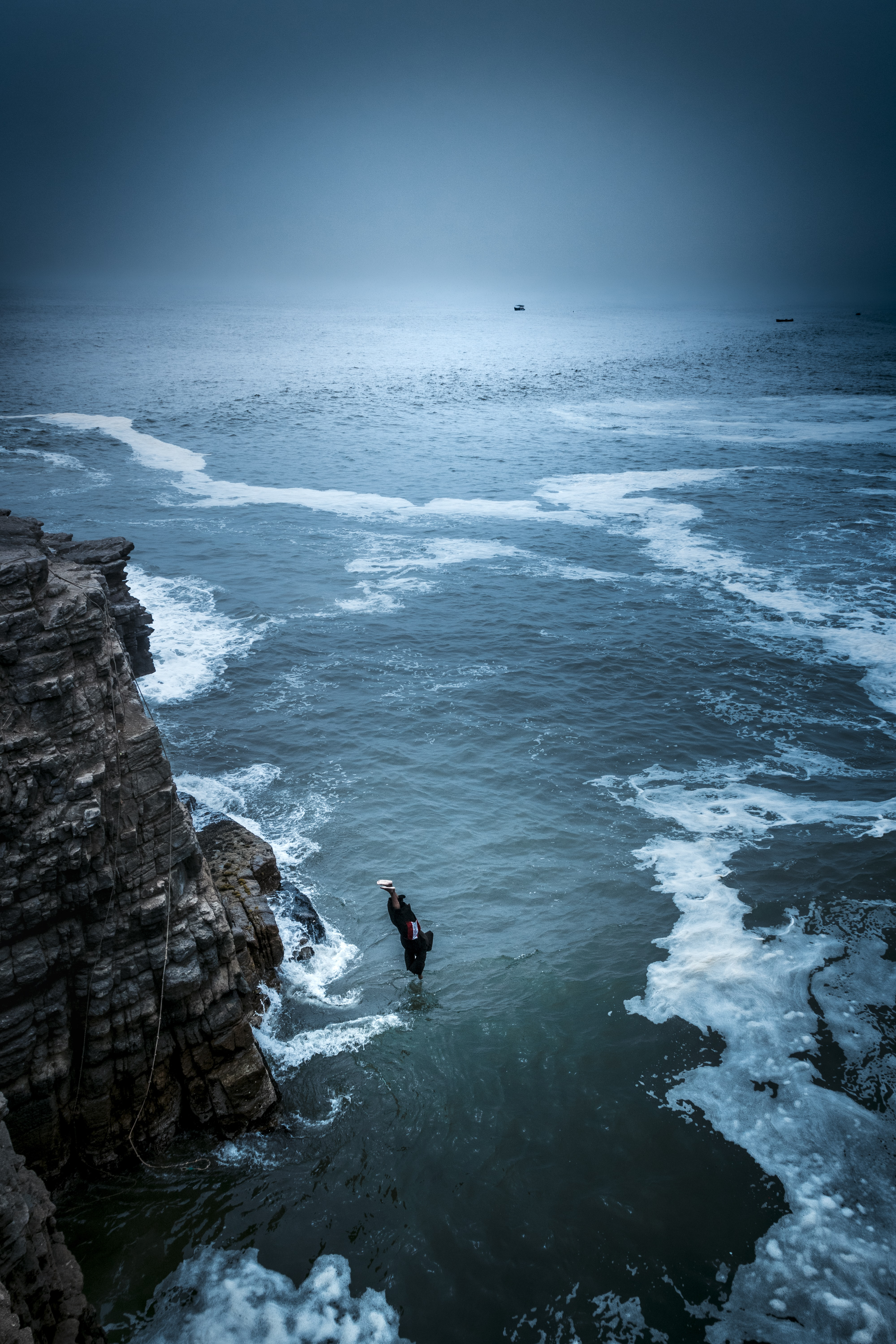 person diving from rock cliff on sea during daytime