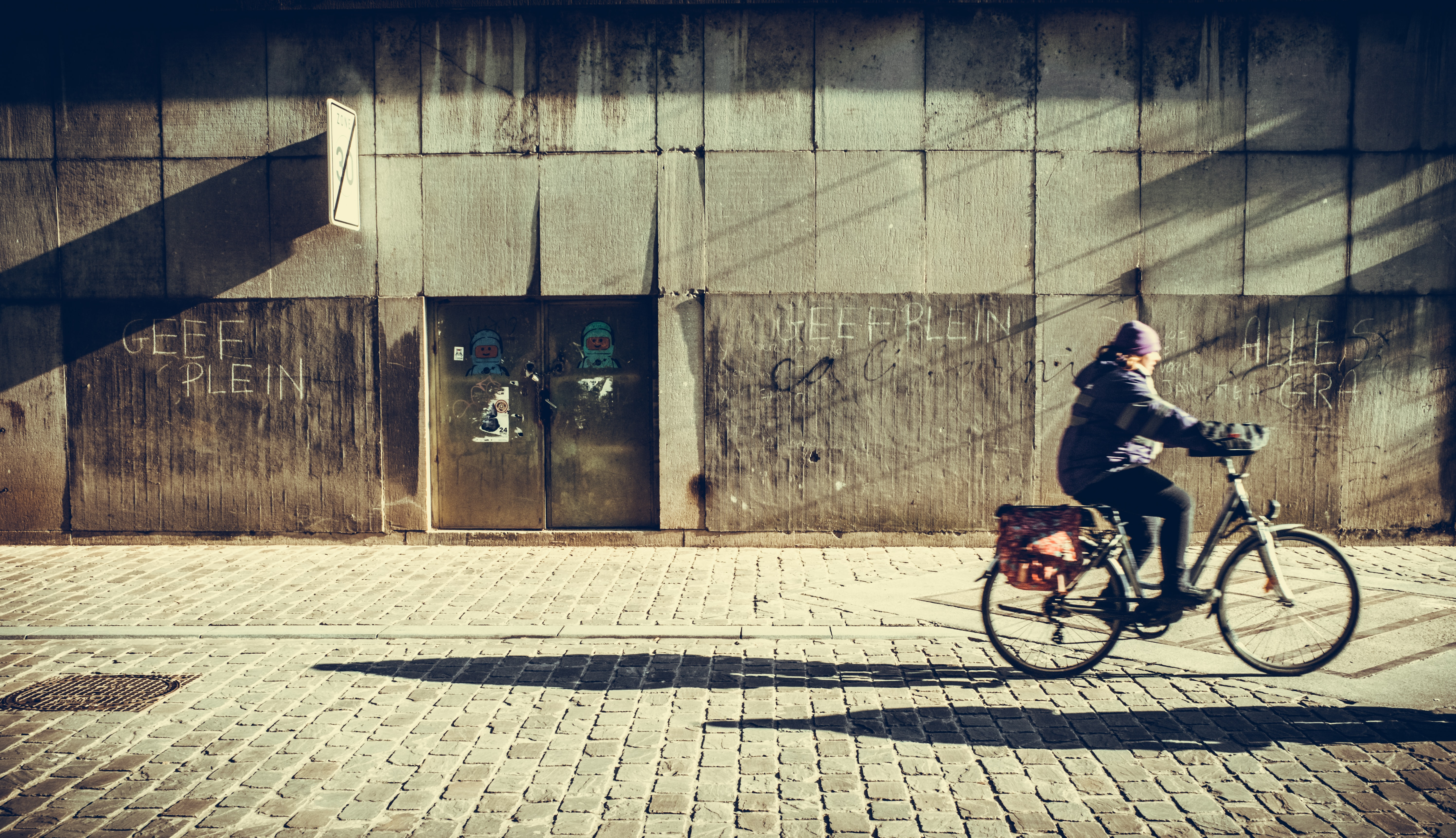 person riding bicycle near concrete wall