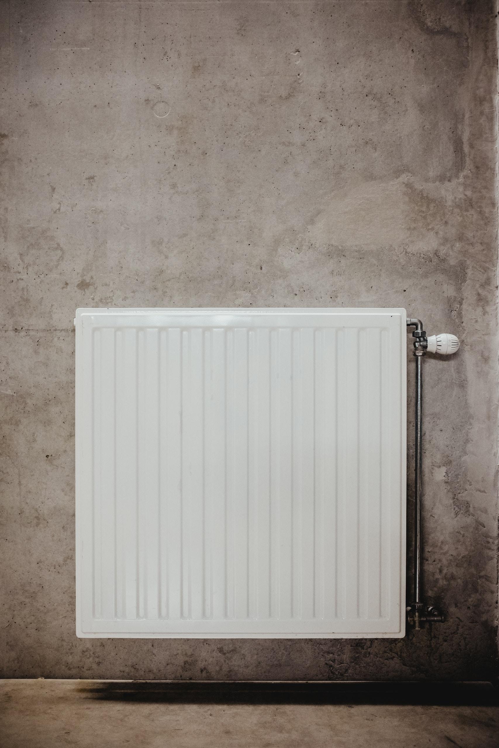 white metal panel heater on gray concrete wall