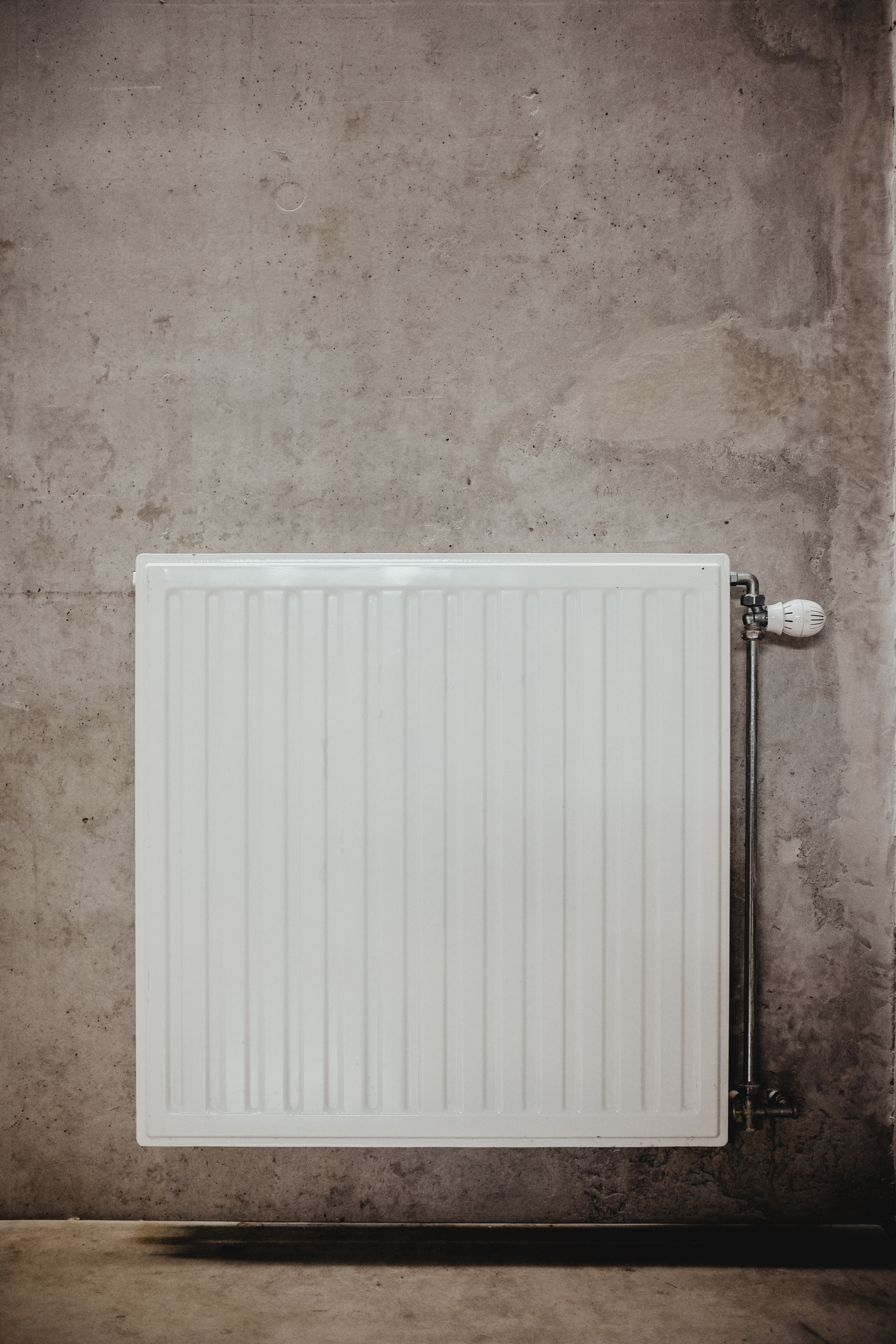 white metal panel heater on gray concrete wall