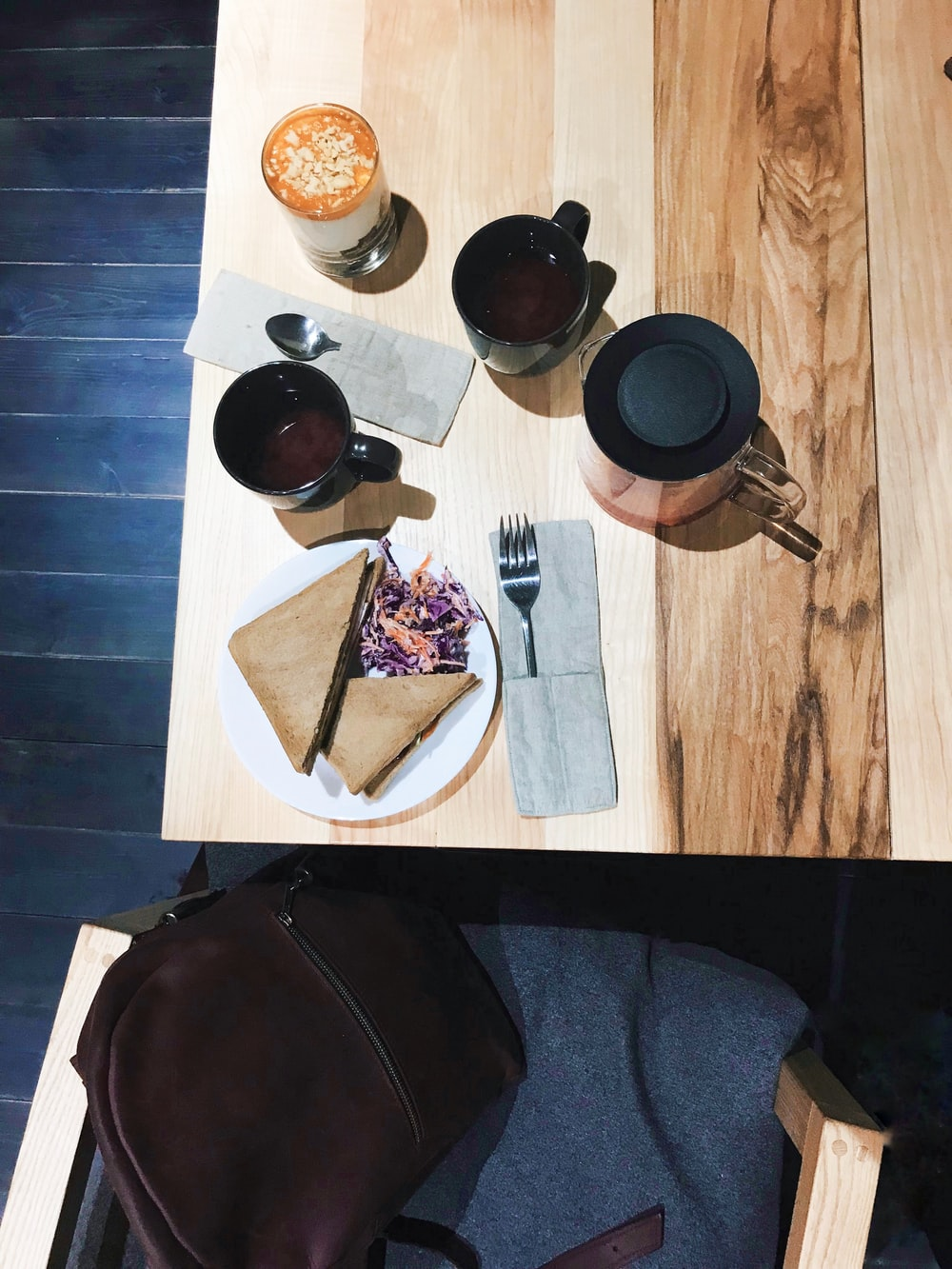 wooden table with cup of coffee and plate of sandwich