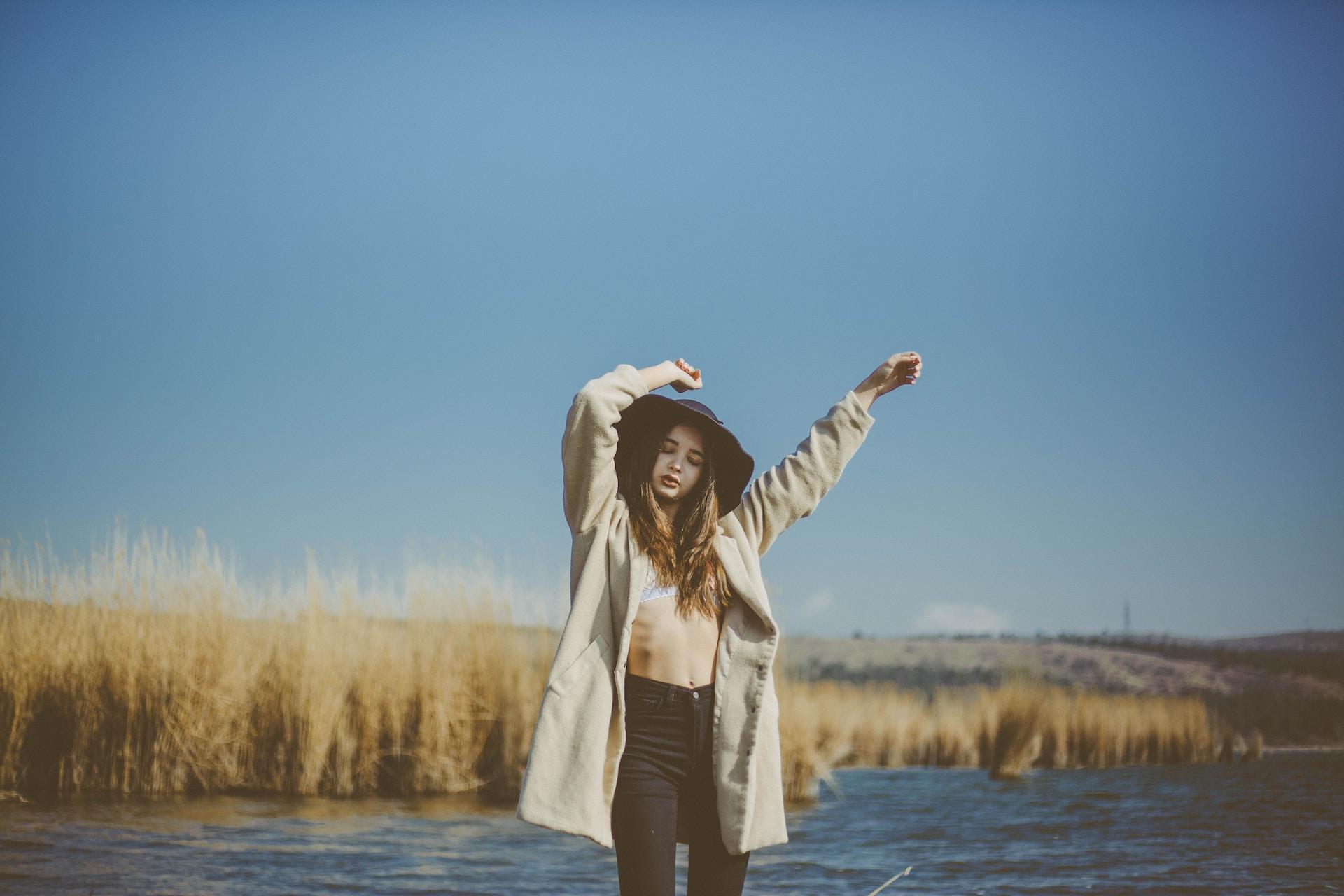 woman wearing coat near body of water