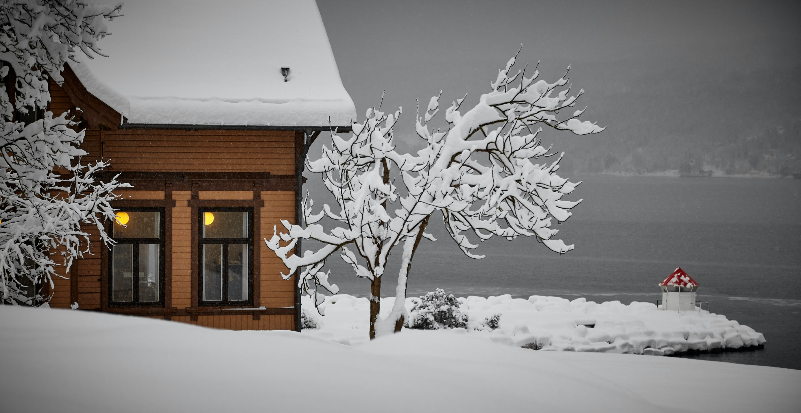 snow covered house on gray lake with lights on in the window