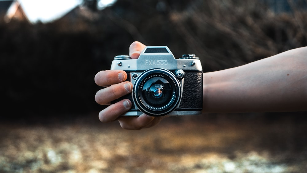 person holding gray camera in selective focus photography