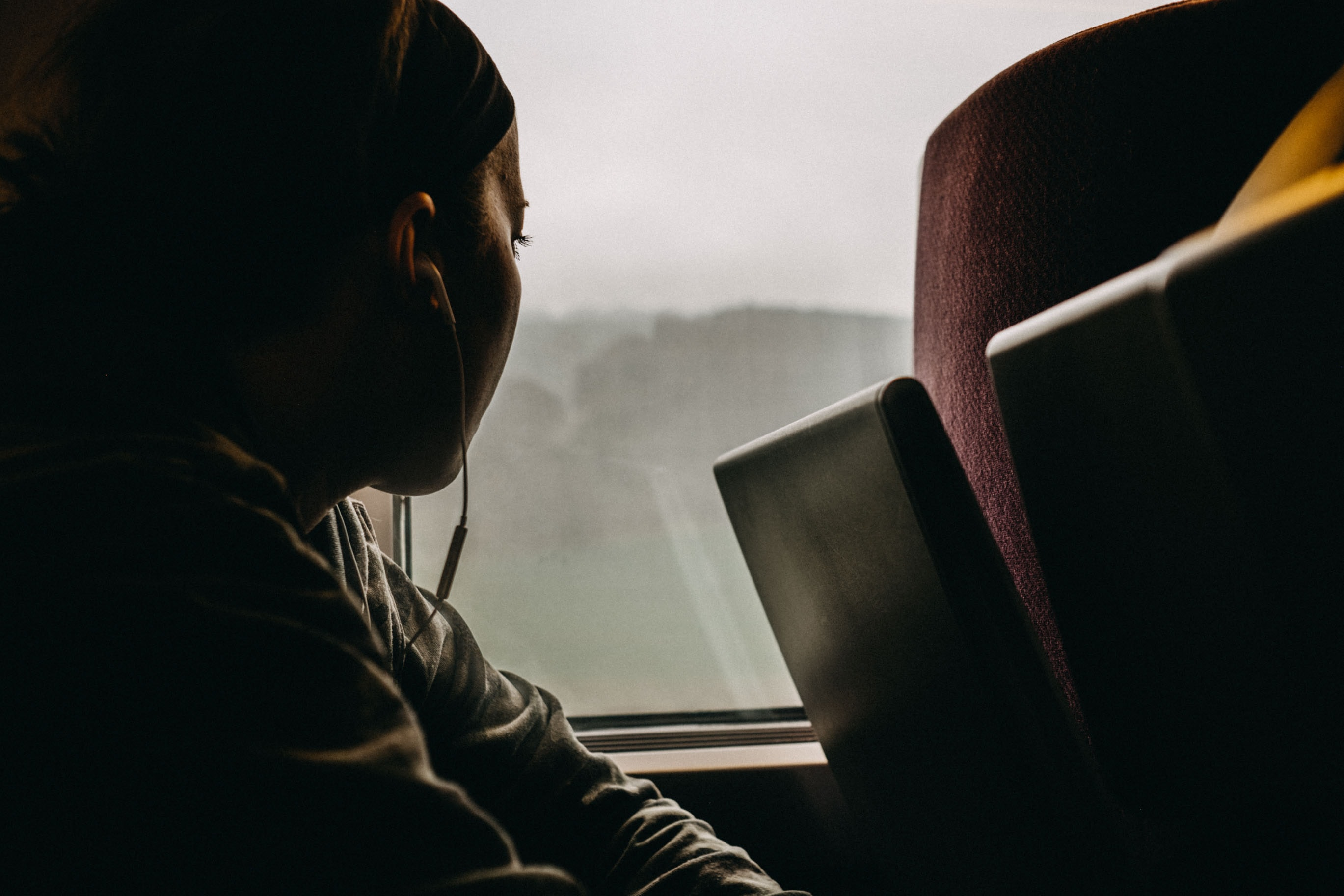 person using earphones looking through window
