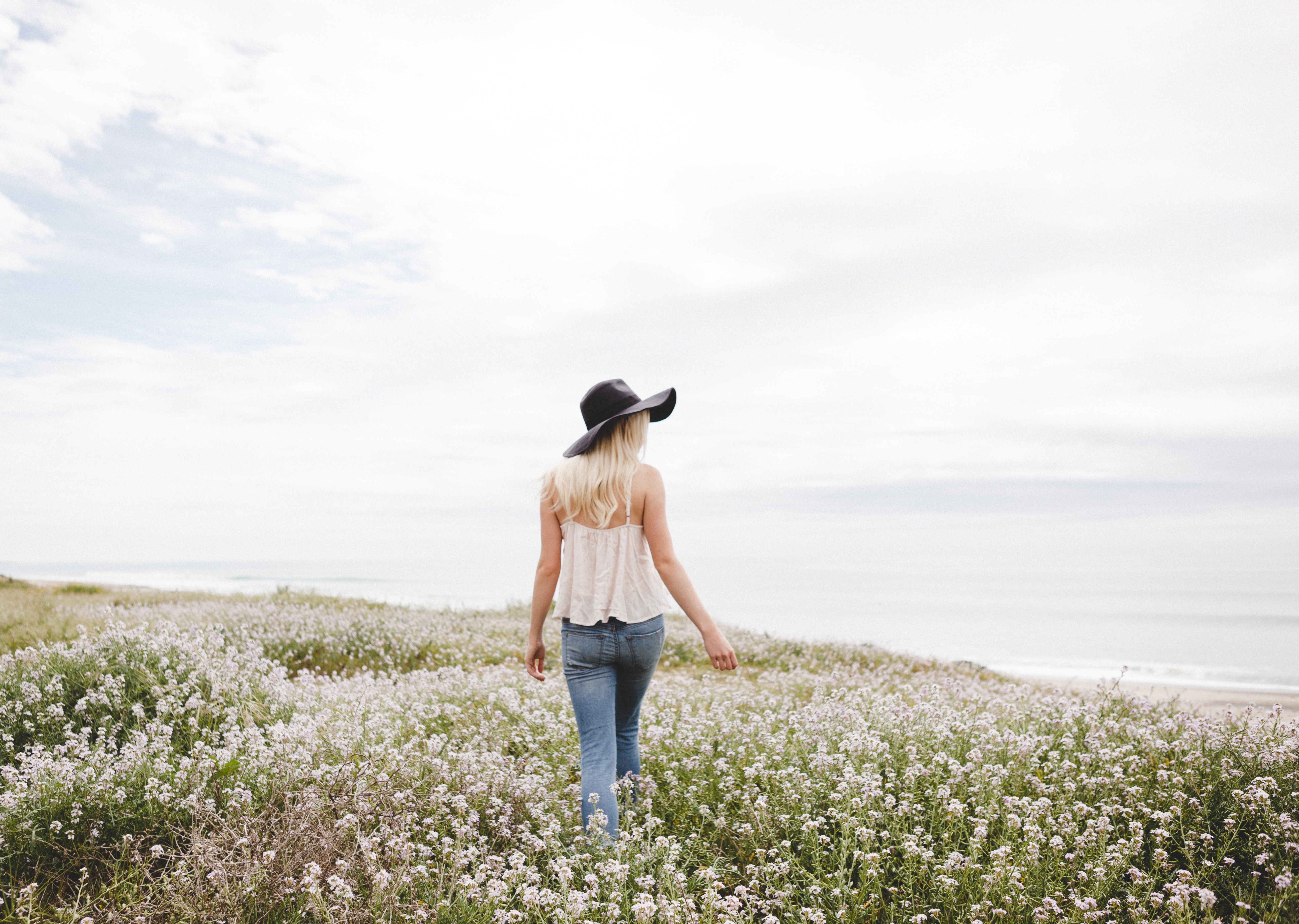 woman wearing black hat walking across the flower field during day time