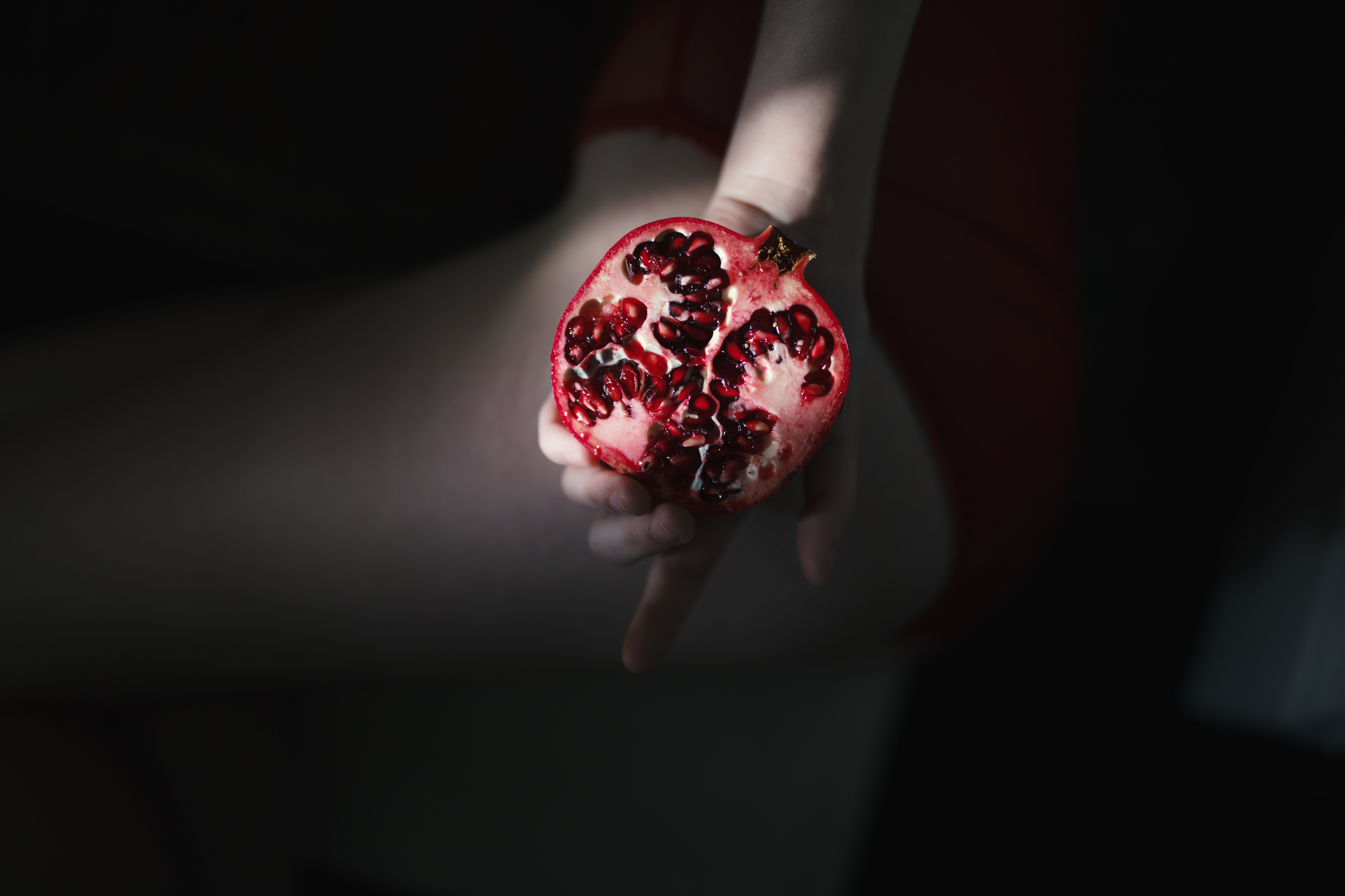 person holding red pomegranate
