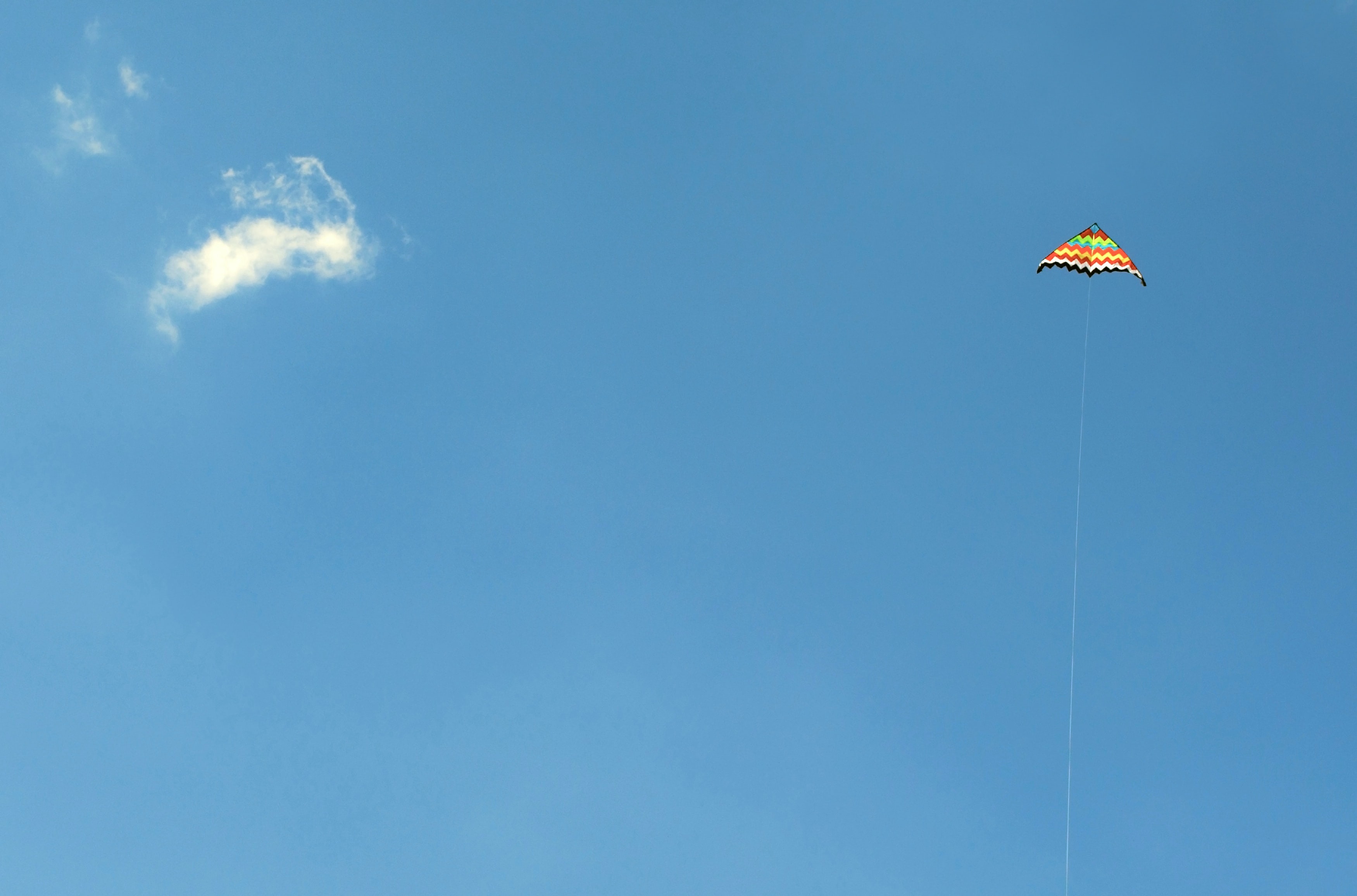 orange and green kite in the sky soaring at daytime