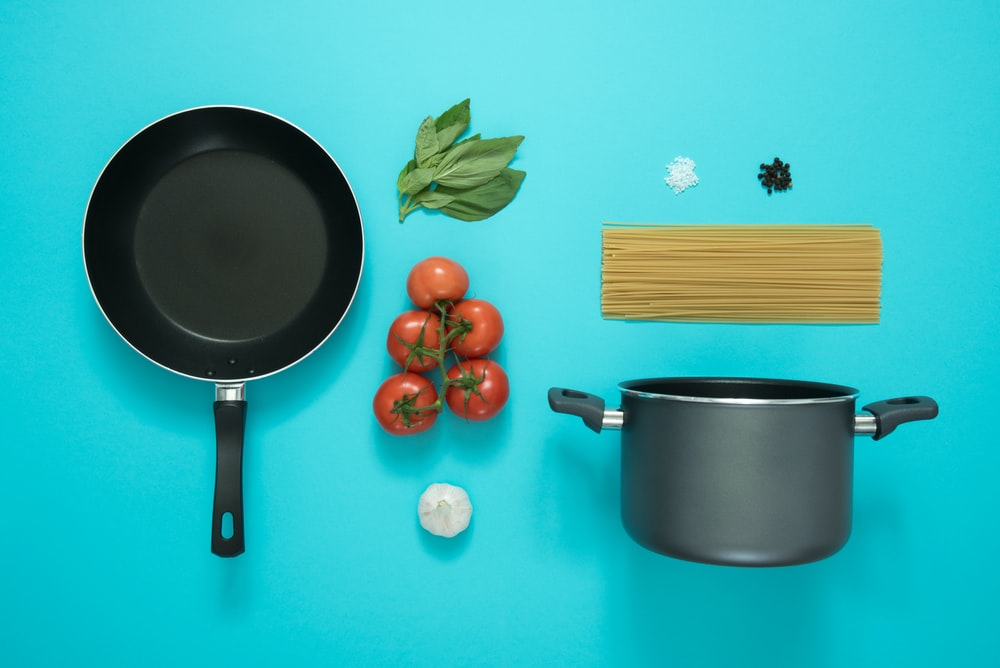 flat lay photography of frying pan beside tomatoes on blue surface