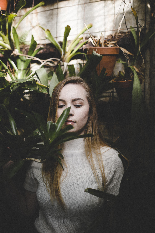 woman wearing white shirt near green plants standing