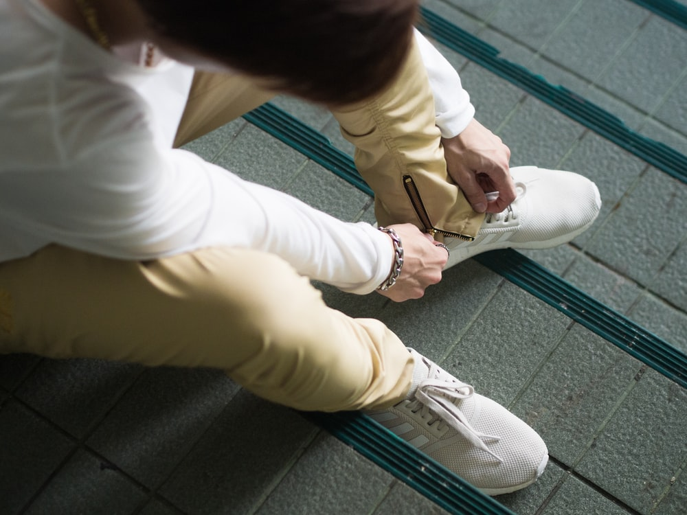 person sitting and zipping his yellow pants