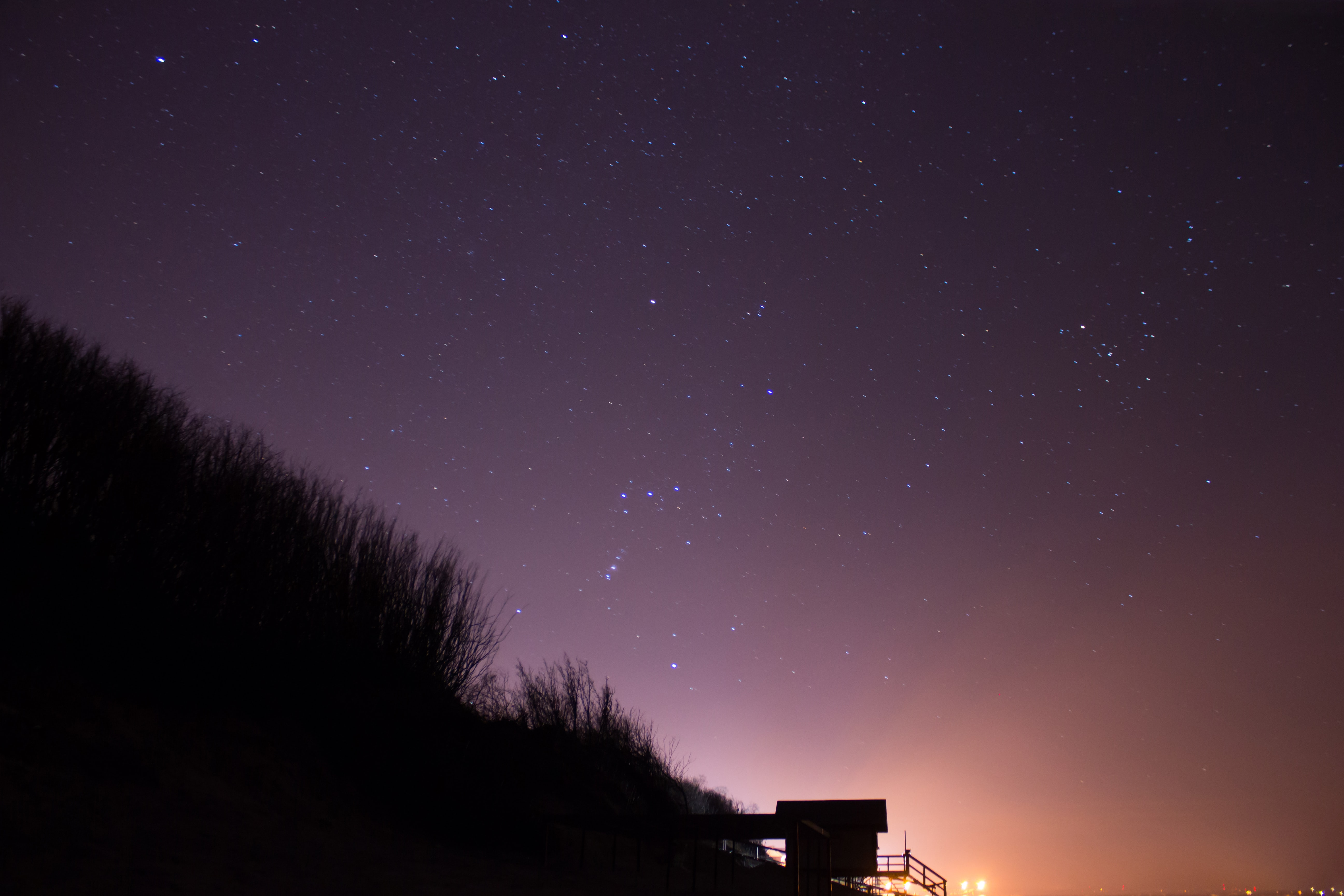 silhouette of shed on mountain under starry sky