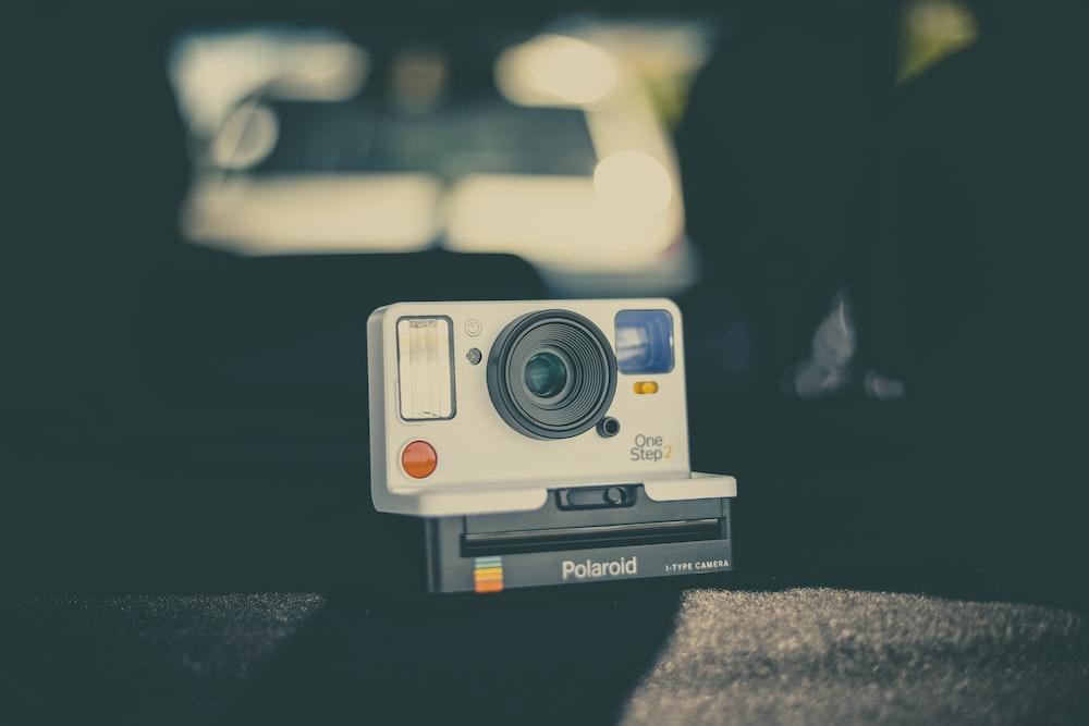 gray and black Polaroid camera on gray surface