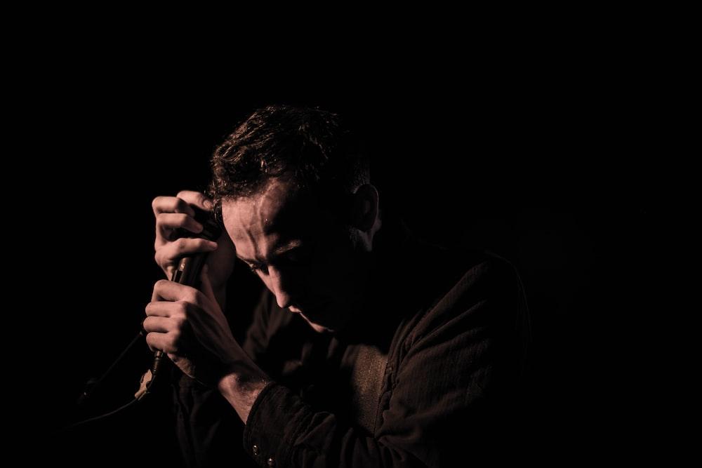 man holding a black dynamic microphone on the dark