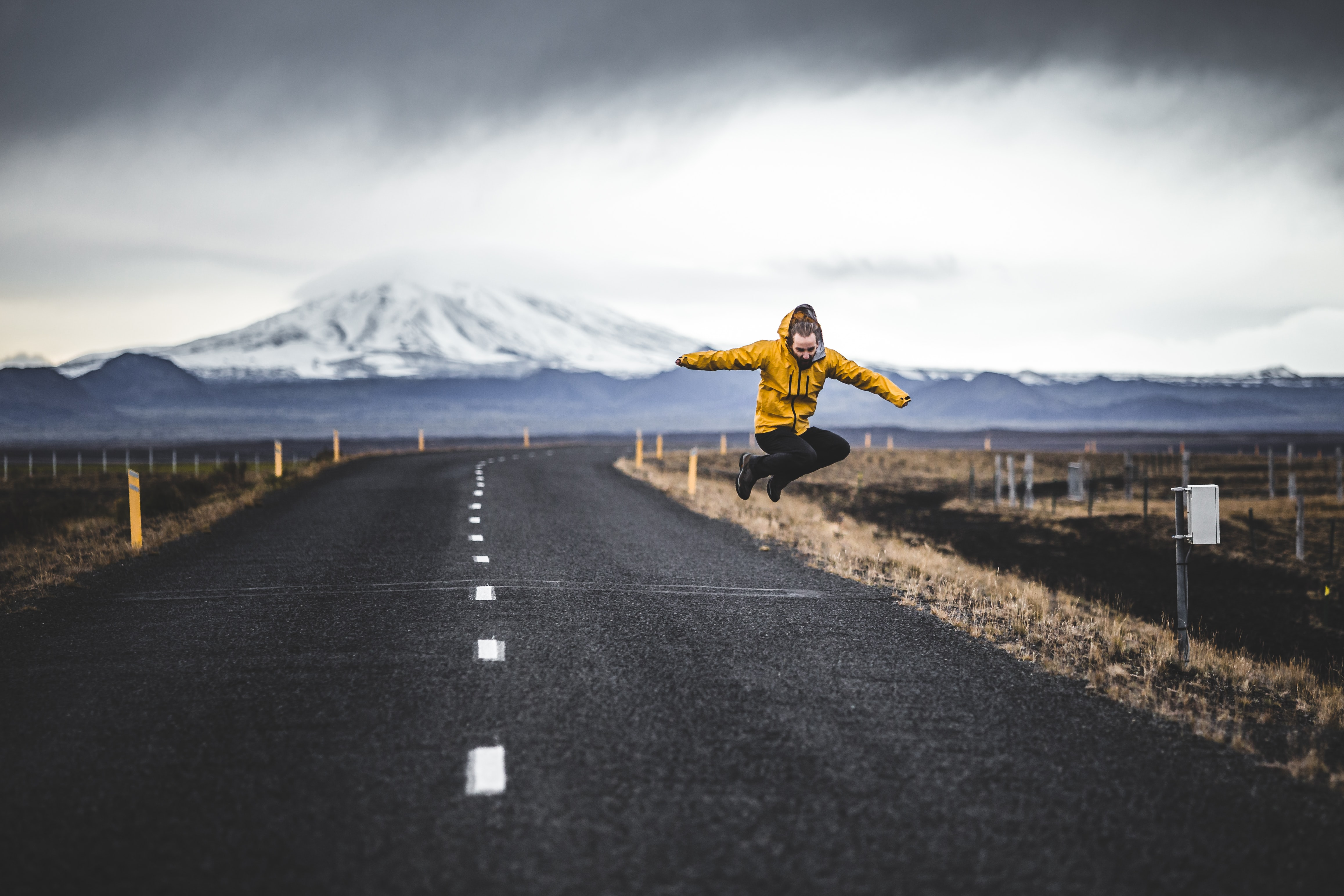 jump shot photo of man over road and mountain alps at distance