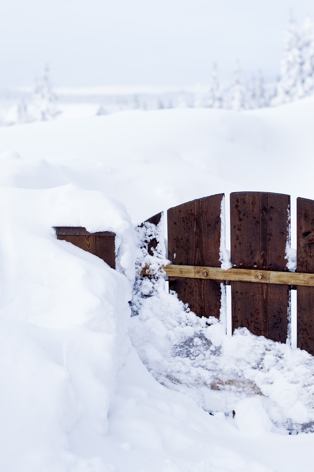 close brown wooden gate surrounding snow
