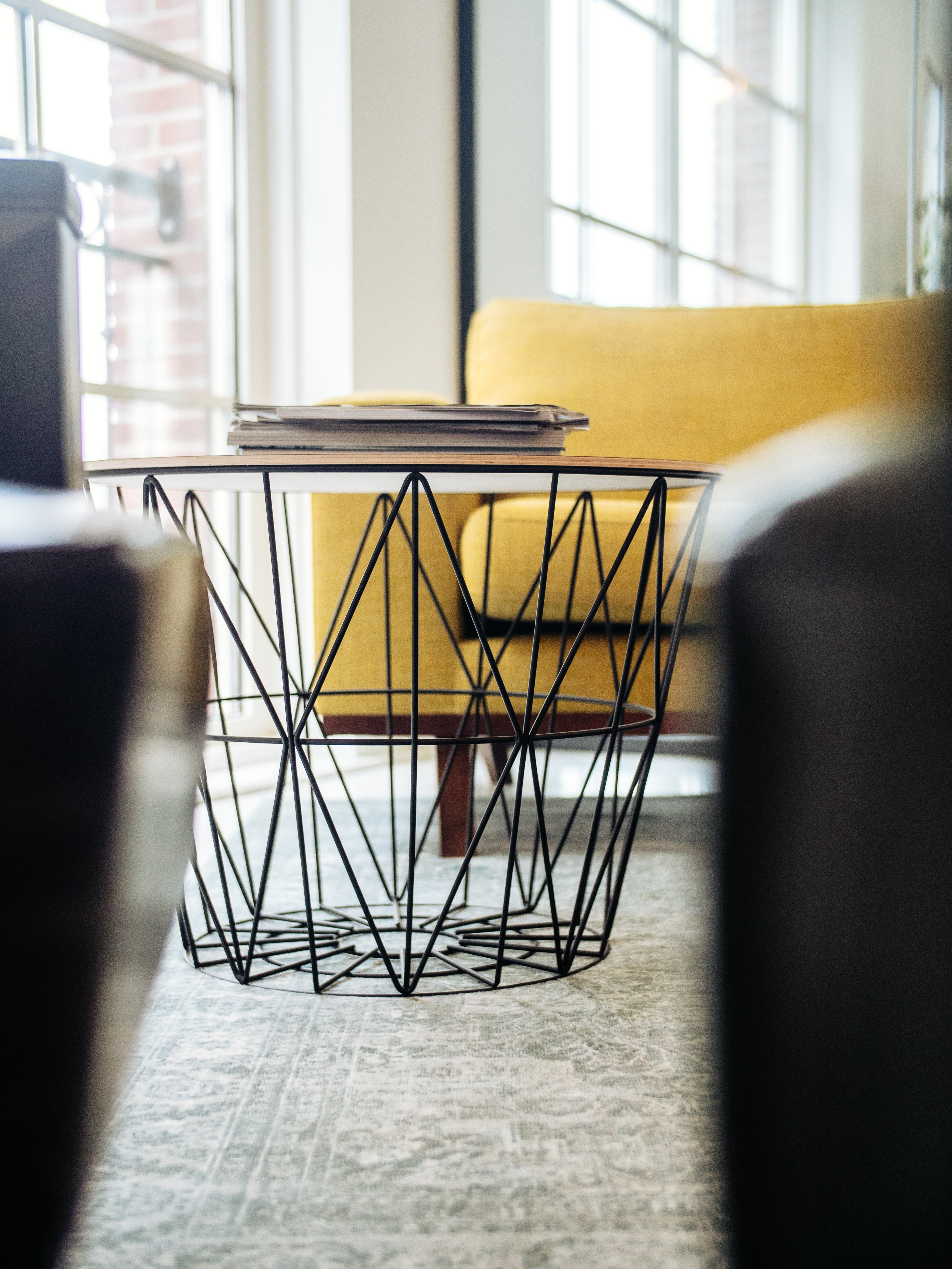 selective focus photography of coffee table beside sofa chair