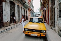 yellow Tofas Murat parked beside white building