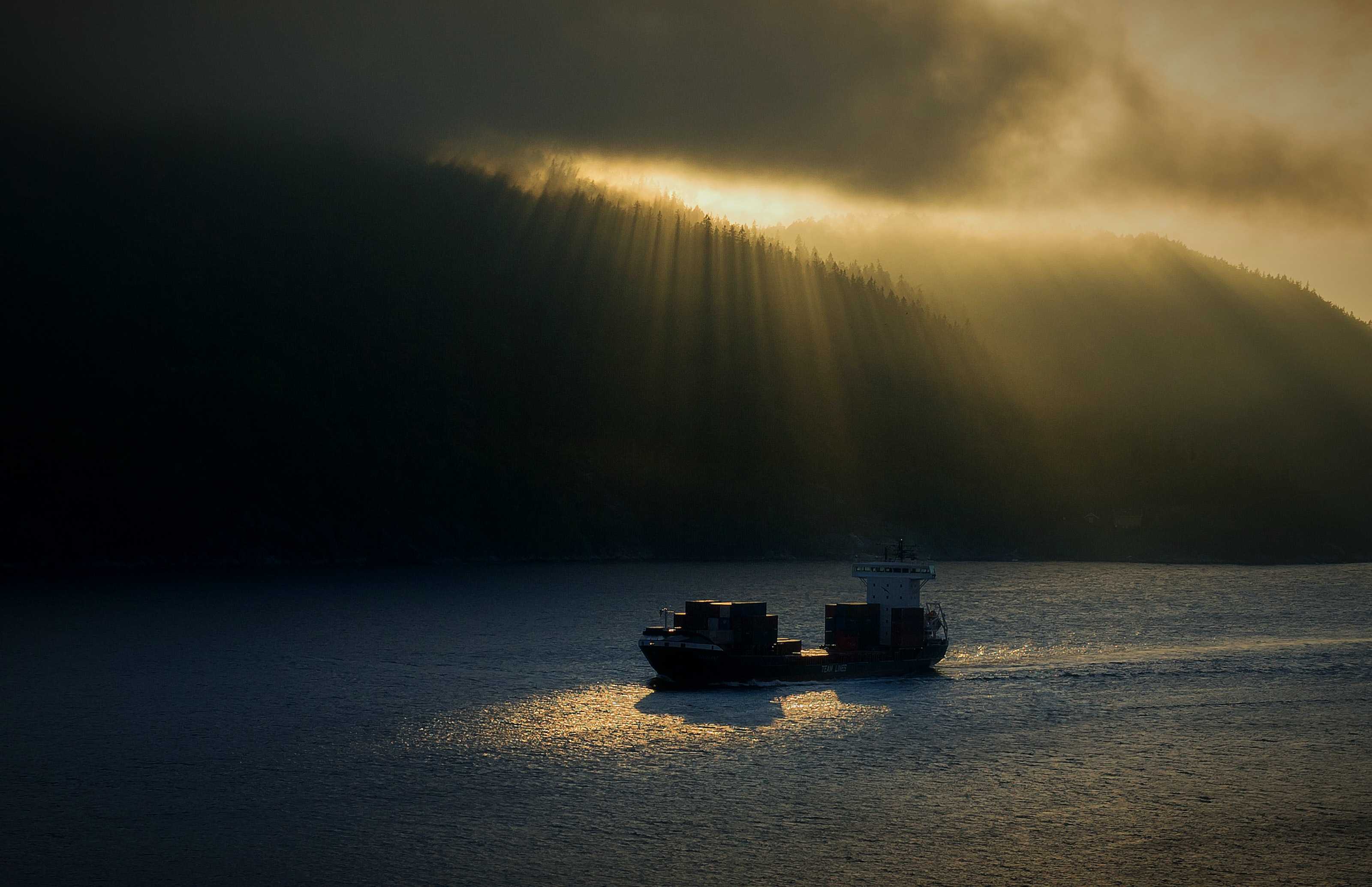 two ships on body of water under cloudy skies during golden hour