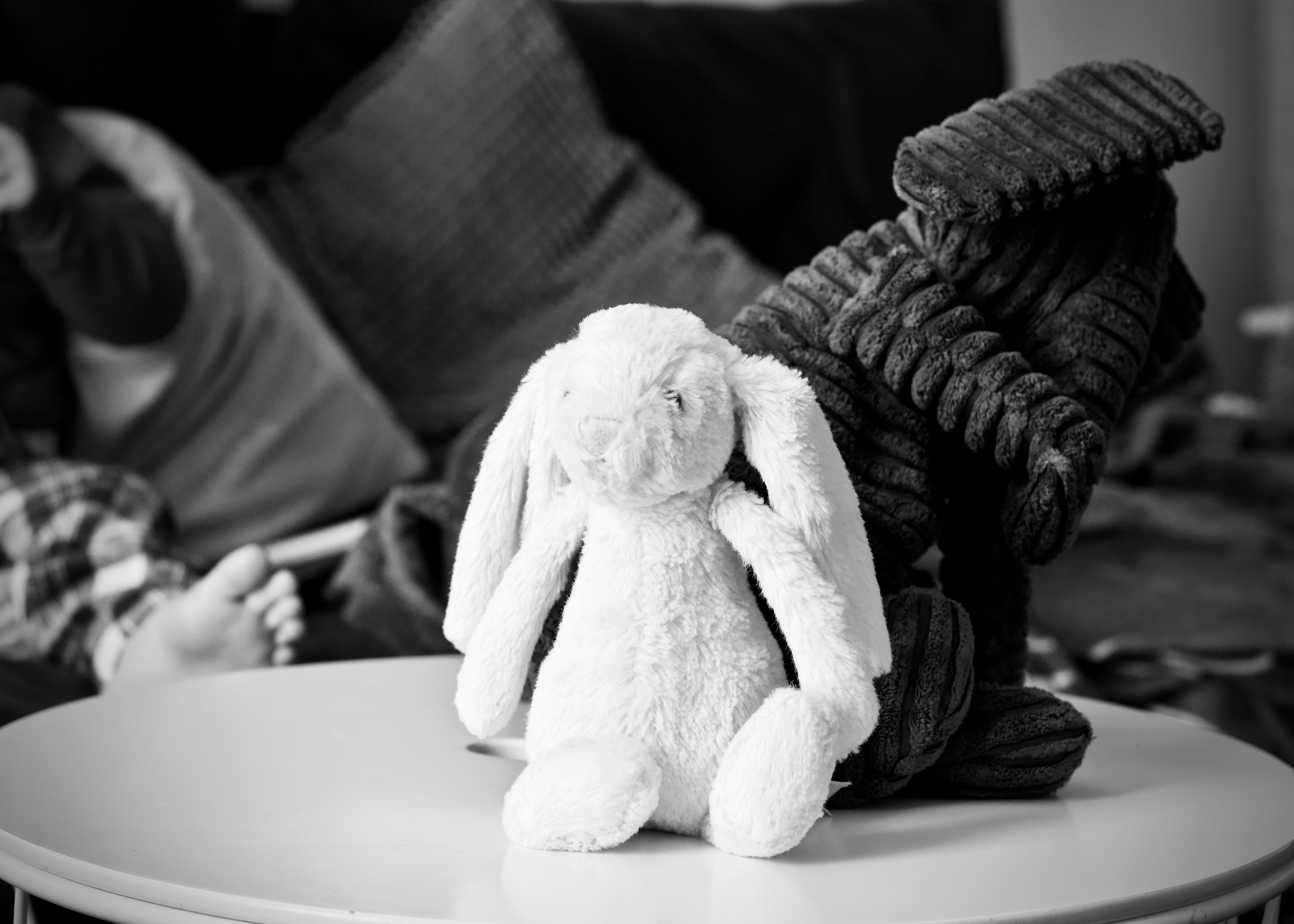 grayscale photography of two rabbit plush toys on top of coffee table