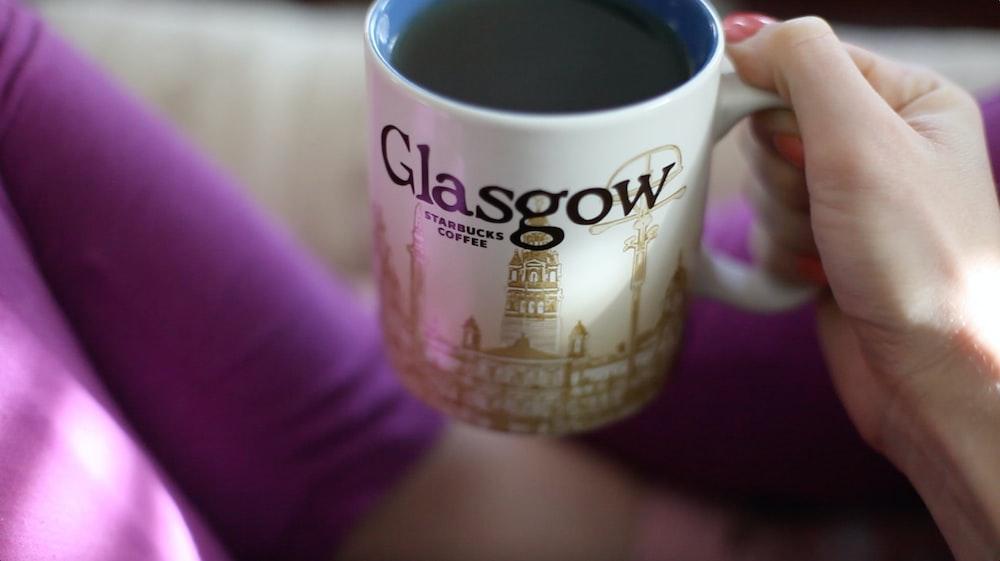 person holding ceramic mug with coffee inside
