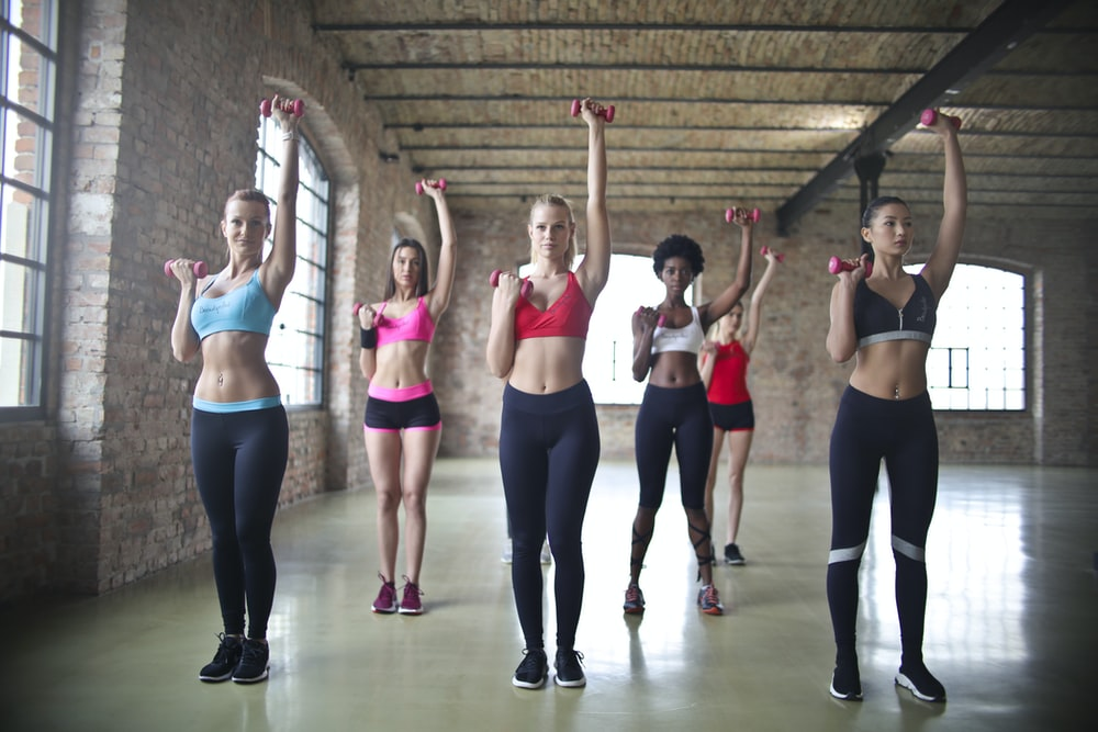 group of women exercise using dumbbells