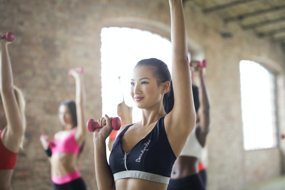 women doing exercise raising left hands while holding dumbbells inside room