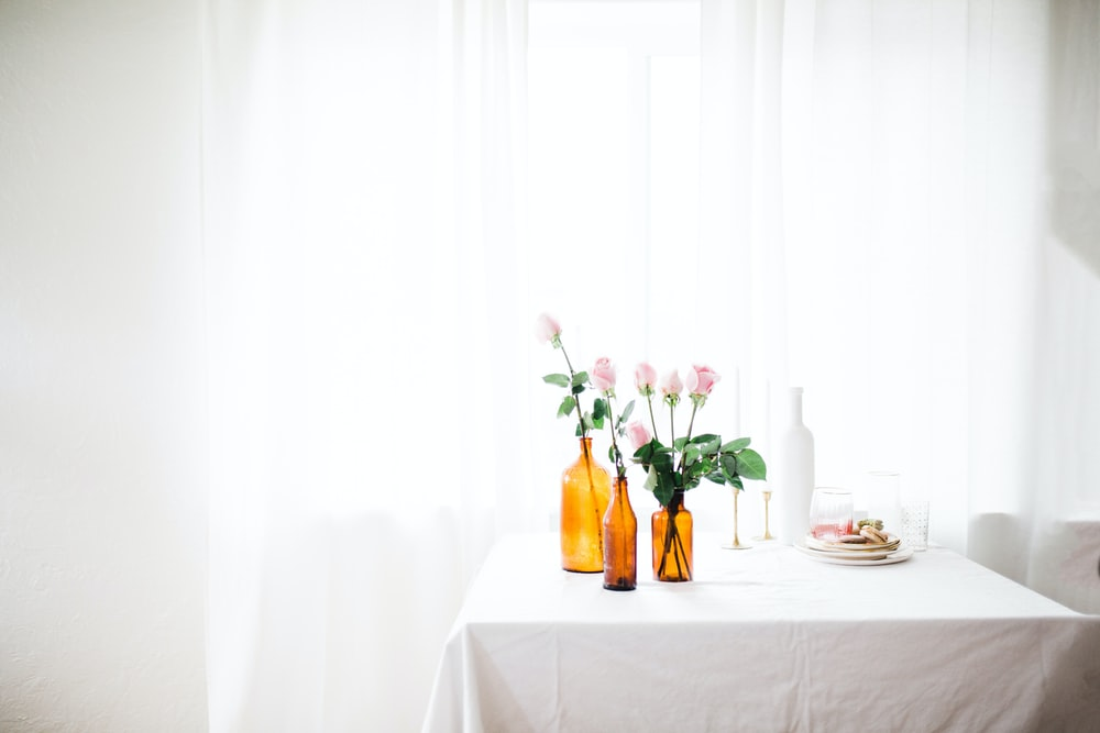 three amber glass flower vase with pink flowers on white table near window curtain