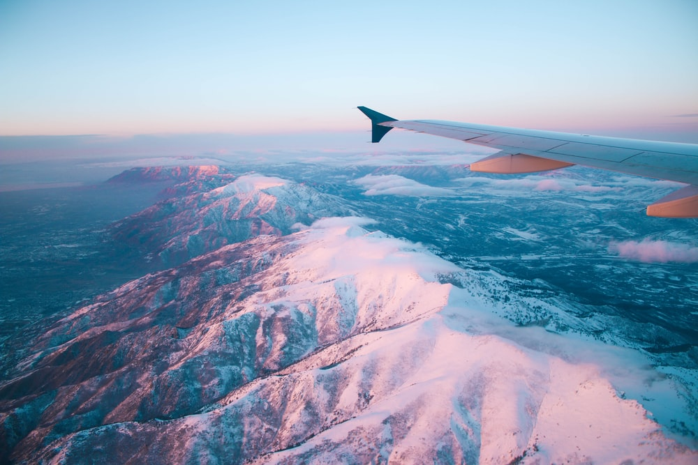 plane flying above white mountains during daytime