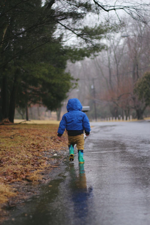 toddler walking on road while raining
