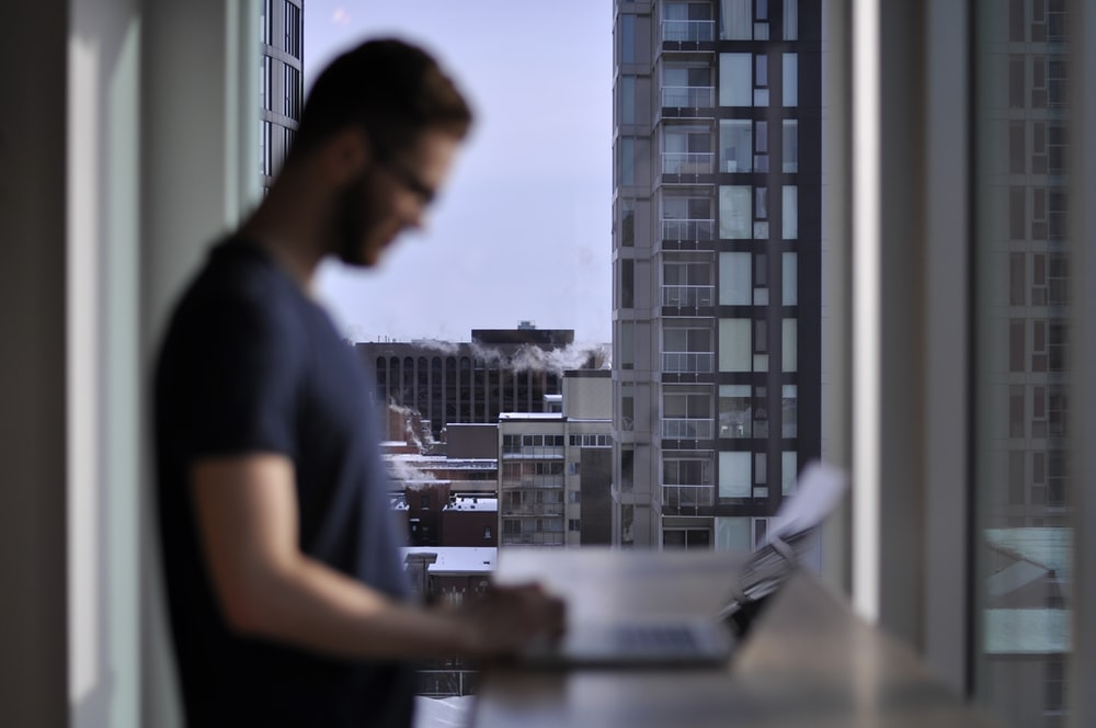 man standing while laptop computer