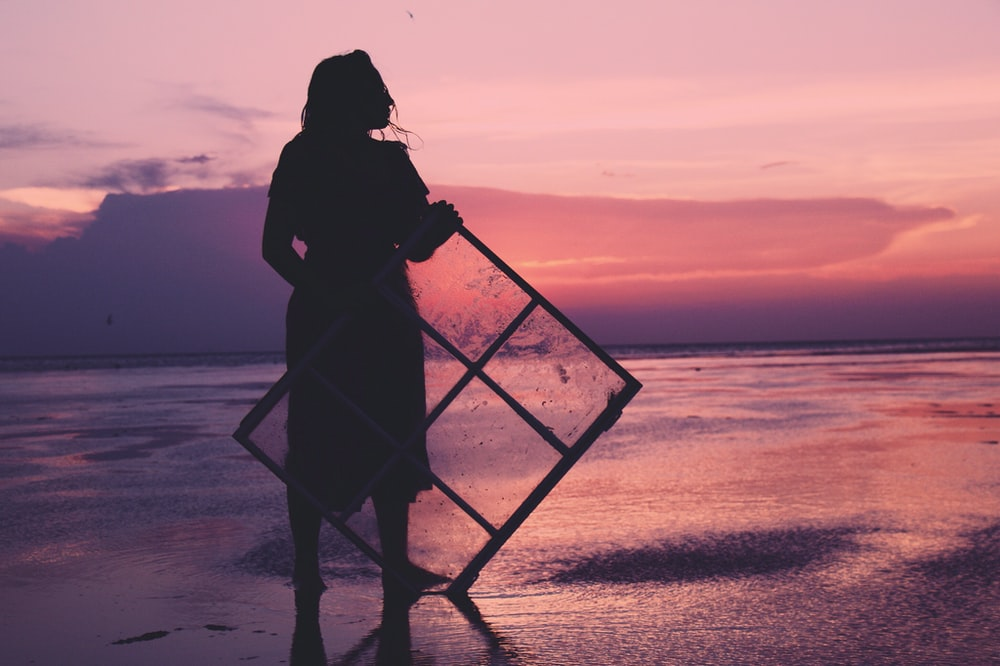 silhouette of woman holding windowpane on shore during golden hour