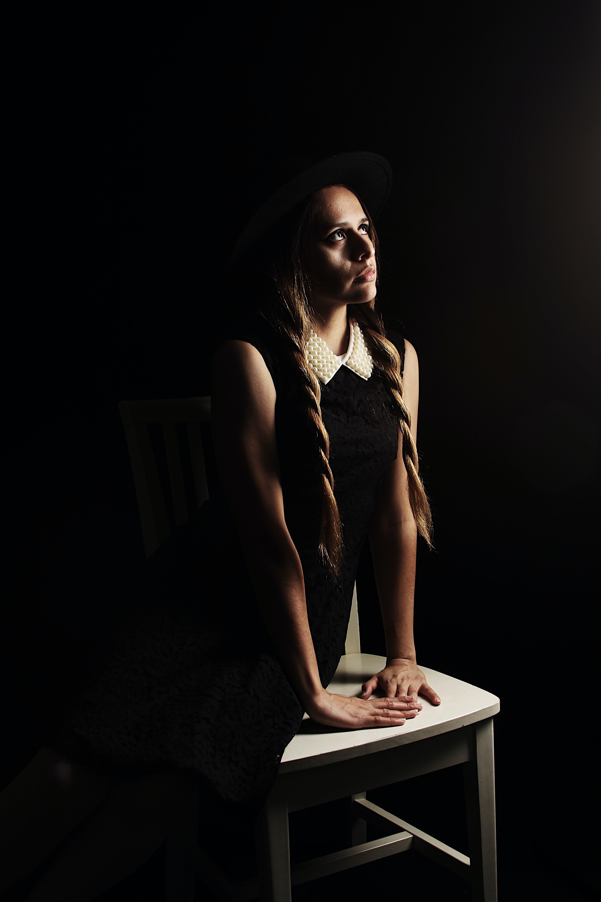 woman looking up sitting on white wooden chair